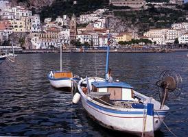 Barcos de pesca con pueblo en la parte trasera, Amalfi, Italia. foto