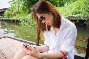 mujer con smartphone en un barco