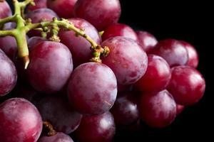 racimo de uvas rojas sobre superficie negra. foto