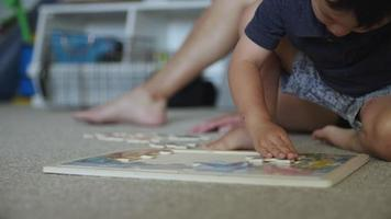 Close up of Asian boy doing puzzle at home
