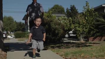 Slow motion of father on skateboard with son running ahead