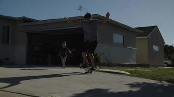 Slow motion of father on skateboard with son running after