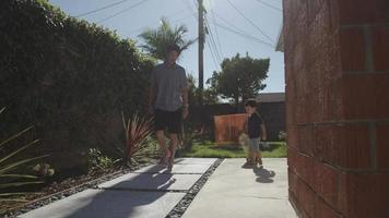 Slow motion of father and son walking with skateboard