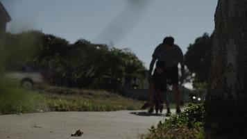 Slow motion of father helping son to ride bike video