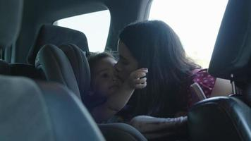 Zeitlupe der Mutter, die Tochter im Autositz küsst video