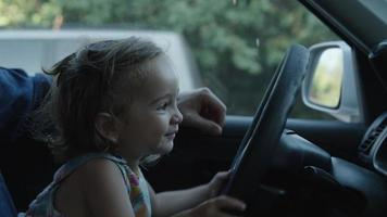 Slow motion of girl playing with steering wheel