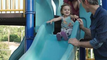 Slow motion of girl about to go down slide