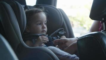 Slow motion of mother putting daughter into car seat video