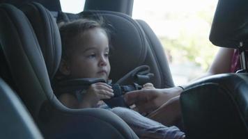 cámara lenta de madre poniendo a su hija en el asiento del coche