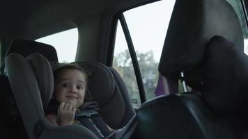 cámara lenta de niña en el asiento del coche sonriendo