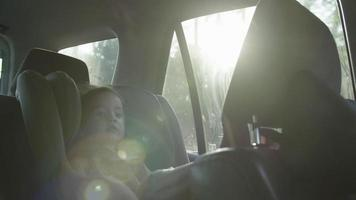 Slow motion of girl in car seat on journey