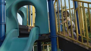 câmera lenta da menina na escalada no parque de jogo