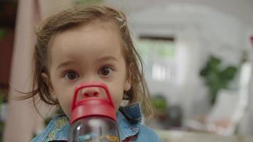 câmera lenta de menina bebendo da garrafa