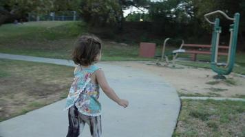 ralenti du père et de la fille en marche dans le parc