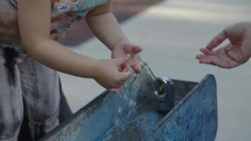 Slow motion of girl touching water in fountain