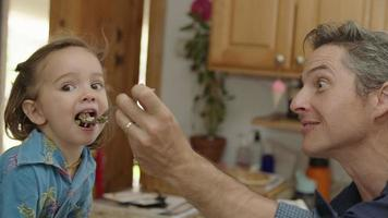 Slow motion of father feeding toddler