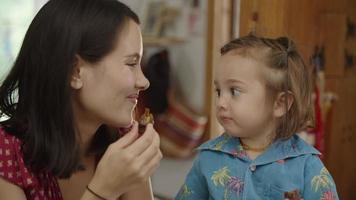 cámara lenta de madre comiendo bocadillos con hija