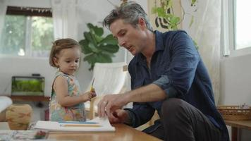 Slow motion of father preparing art supplies for daughter