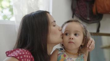 Slow motion of mother kissing daughter