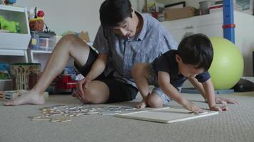 Father and young son doing puzzle at home