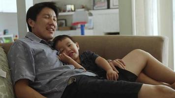Father cuddling young son on couch at home video