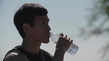 Cámara lenta de hombre adulto medio bebiendo agua después del ejercicio