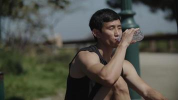 Mid adult man drinking water after exercise