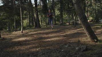 Slow motion of young woman running in woods