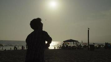 cámara lenta de hombres jugando con pelota en la playa
