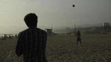 Slow motion of men playing with ball on beach