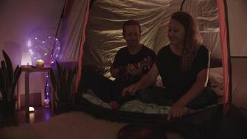 Slow motion of couple sitting in tent playing music