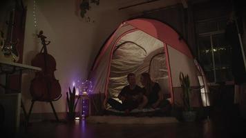câmera lenta de casal sentado na barraca com o violão em casa