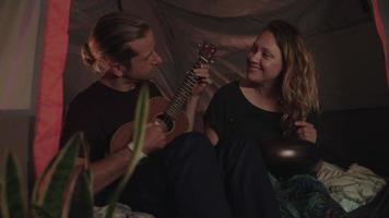 Zeitlupe des liebenden Paares mit Gitarre im Zelt