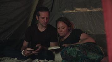 Cámara lenta de pareja en tienda de campaña con teléfono y libro de lectura video