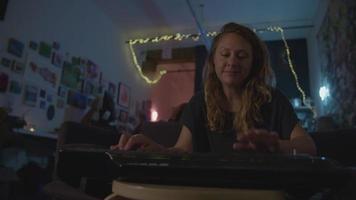 câmera lenta de mulher tocando teclado à noite