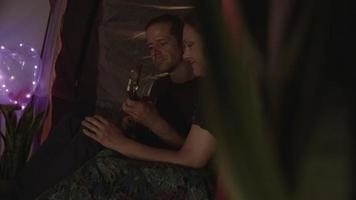 câmera lenta de um casal apaixonado com guitarra na barraca