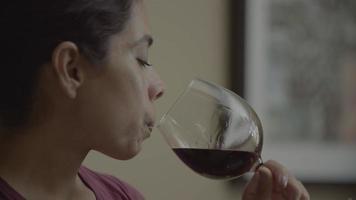 Cámara lenta de mujer adulta media bebiendo vino tinto