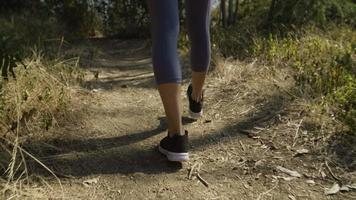 Slow motion of woman wearing training shoes walking on track
