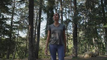 Slow motion of young woman walking through woods