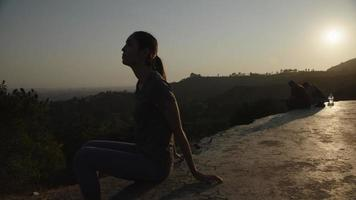 Slow motion of woman sitting at sunset