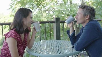 Slow motion of couple drinking coffee on terrace