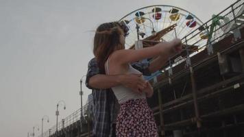 Zeitlupe des jungen Paares, das durch Riesenrad küsst video