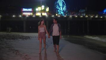 Zeitlupe des jungen Paares, das nachts durch Vergnügungspark geht video