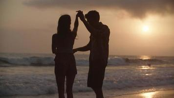 Slow motion of young couple dancing on beach