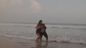 Zeitlupe des jungen Mannes, der Frau huckepack am Strand gibt video