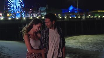 Cámara lenta de la joven pareja caminando por el parque de atracciones por la noche video
