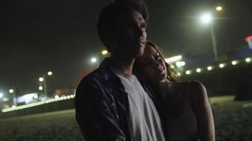 Cámara lenta de amorosa pareja joven en la playa por la noche video