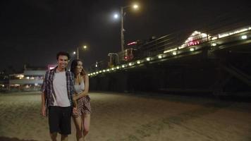 Cámara lenta de pareja joven caminando pareja cogidos de la mano por la noche video