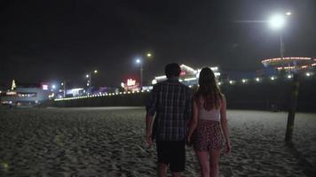 Cámara lenta de la joven pareja cogidos de la mano caminando en la playa por la noche video