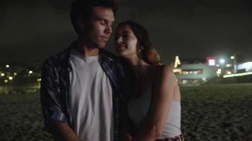 Cámara lenta de la joven pareja besándose en la playa por la noche